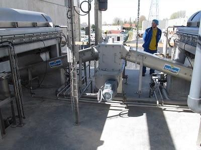 View of 2 sludge conveyors under decanter centrifuges
